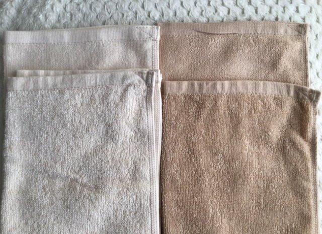8年タオルの洗濯前後の比較画像。手前が洗濯後でパイルが立ちタオルに少し厚みが出てきた。インターロック縫いも写っている。